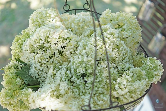 Blomster i kurv hengende over hagebordet